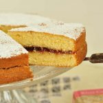 Classic Victoria Sponge Cake on stand slice and book