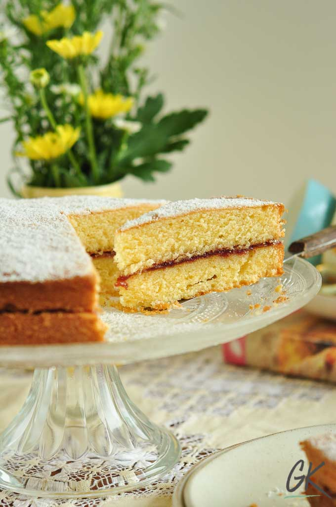Classic Victoria Sponge Cake slice on stand with flowers